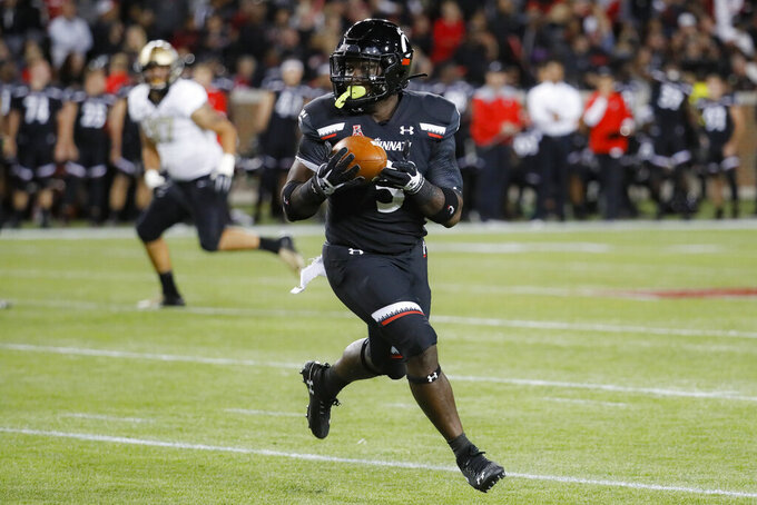 Cincinnati running back Michael Warren II (3) carries the first half of the team's NCAA college football game against UCF, Friday, Oct. 4, 2019, in Cincinnati. (AP Photo/John Minchillo)