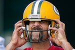 FILE - Green Bay Packers' Aaron Rodgers puts on his helmet during NFL football training camp in Green Bay, Wis., in this Saturday, Aug. 15, 2020, file photo. Aaron Rodgers has made it to Green Bay on the eve of the Packers' first training-camp workout. Rodgers was seen arriving at Lambeau Field on Tuesday morning, July 27, 2021, the day after NFL Network and ESPN reported the reigning MVP was closing in on a deal that would keep him with the Packers this season.  (AP Photo/Morry Gash, Fiule)