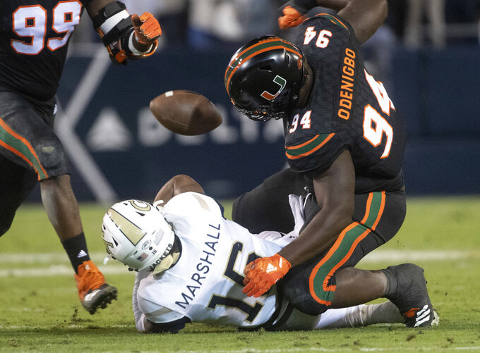 Miami defensive lineman Tito Odenigbo (94) forces a fumble by Georgia Tech quarterback TaQuon Marshall during the first half of an NCAA college football game Saturday, Nov. 10, 2018, in Atlanta. (AP Photo/John Amis)