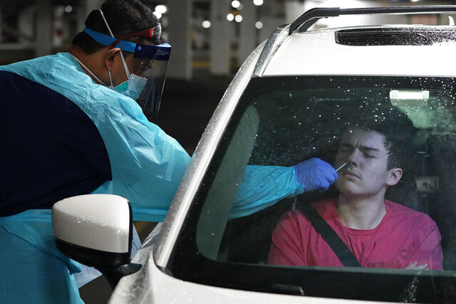 Brendan Hurley, a junior in high school, is tested for COVID-19 at a drive-through testing site in a parking garage in West Nyack, N.Y., Monday, Nov. 30, 2020. The site was only open to students and staff of Rockland County schools in an effort to test enough people to keep the schools open for in-person learning. (AP Photo/Seth Wenig)