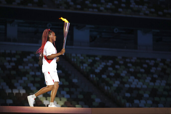 Naomi Osaka carries the Olympic Torch during the opening ceremony in the Olympic Stadium at the 2020 Summer Olympics, Friday, July 23, 2021, in Tokyo, Japan. (Hannah McKay/Pool Photo via AP)