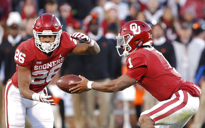 Oklahoma quarterback Kyler Murray (1) hands off the ball to Oklahoma running back Kennedy Brooks (26) during a play against Oklahoma State in the second half of an NCAA college football game in Norman, Okla., Saturday, Nov. 10, 2018. Oklahoma won 48-47. (AP Photo/Alonzo Adams)