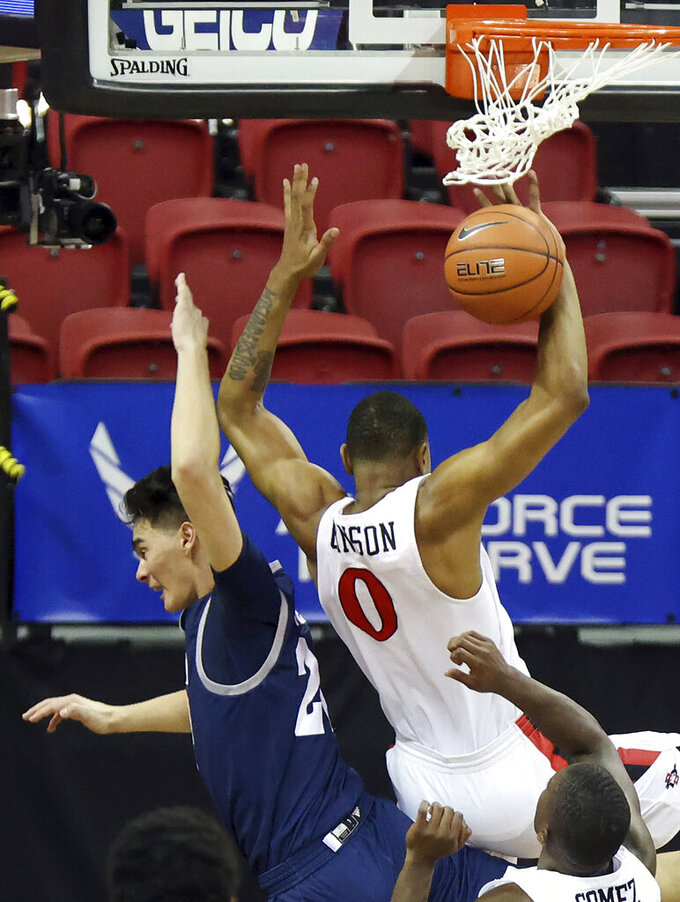 San Diego State forward Keshad Johnson (0) fouls Nevada guard Daniel Foster (20) during the first half of an NCAA college basketball game in the semifinal round of the Mountain West Conference men's tournament Friday, March 12, 2021, in Las Vegas. (AP Photo/Isaac Brekken)
