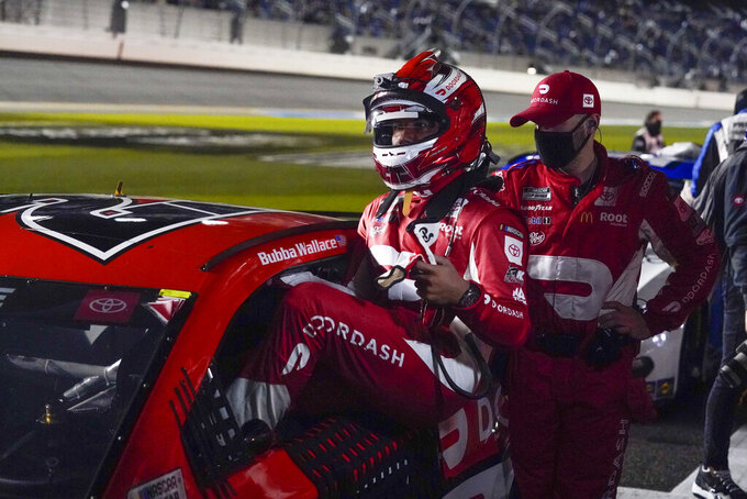 Bubba Wallace gets into his car after a weather delay during the NASCAR Daytona 500 auto race at Daytona International Speedway, Sunday, Feb. 14, 2021, in Daytona Beach, Fla. (AP Photo/John Raoux)