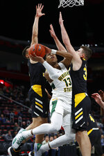 Wright State guard Malachi Smith (13) drives between Northern Kentucky guard Paul Djoko and forward Drew McDonald (34) during the first half of an NCAA college basketball game for the Horizon League men's tournament championship in Detroit, Tuesday, March 12, 2019. (AP Photo/Paul Sancya)