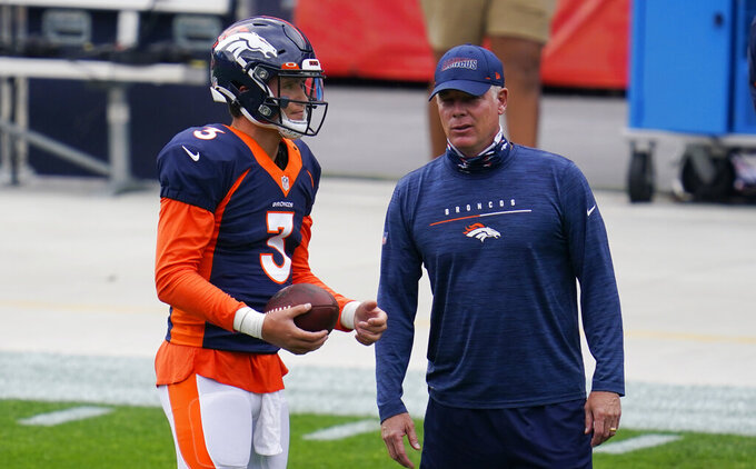 Denver Broncos quarterback Drew Lock, left, confers with offensive coordinator Pat Shurmur during an NFL football practice in empty Empower Field at Mile High, Saturday, Aug. 29, 2020, in Denver. (AP Photo/David Zalubowski)