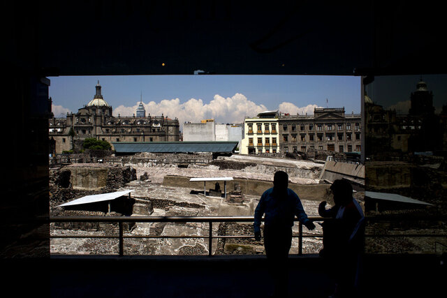 FILE - In this Friday, Aug. 7, 2015 file photo, a worker stands in front of ongoing excavations at the Templo Mayor archeological site, directing people into the adjoining museum in downtown Mexico City, once the Aztec capital of Tenochtitlan. In light of the 2020 COVID-19 pandemic, it remains unclear how much humanity has learned from one of the greatest mass die-offs due to the smallpox epidemic, which gave rise to the first successful vaccine in 1796. (AP Photo/Rebecca Blackwell, File)