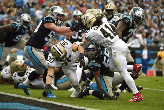 Carolina Panthers middle linebacker Luke Kuechly (59) tries to stop New Orleans Saints running back Alvin Kamara (41) as Kamara scores a touchdown during the first half of an NFL football game in Charlotte, N.C., Sunday, Dec. 29, 2019. (AP Photo/Mike McCarn)