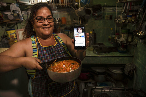 """Contributor Yuliet Colon poses for a photo holding a pot of her creation, """"Cuban-style pisto manchego,""""  and her phone that displays the Facebook page, """"Recipes from the Heart,"""" in her home in Havana, Cuba, Friday, April 2, 2021.  Colon, a 39-year-old mother of two, found for herself a solution that combines ingenuity with the innovative use of the Internet and became a contributor to """"Recipes from the Heart,"""" with tips, ideas and tricks to get ahead with items that are actually available at the market. (AP Photo/Ramon Espinosa)"""