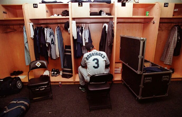 FILE - In this Oct. 5, 1997, file photo, Seattle Mariners' Alex Rodriguez sits in the locker room following their 3-1 loss to the Baltimore Orioles in Game 4 of the American League Division Series at Camden Yards in Baltimore. The Seattle Mariners are the only baseball franchise never to advance to the Fall Classic. Baseball has never been played in Seattle beyond Oct. 22. The Mariners have three times been to the American League Championship Series, and all three times were sent home before there could ever be a Game 7. (AP Photo/Doug Mills, File)