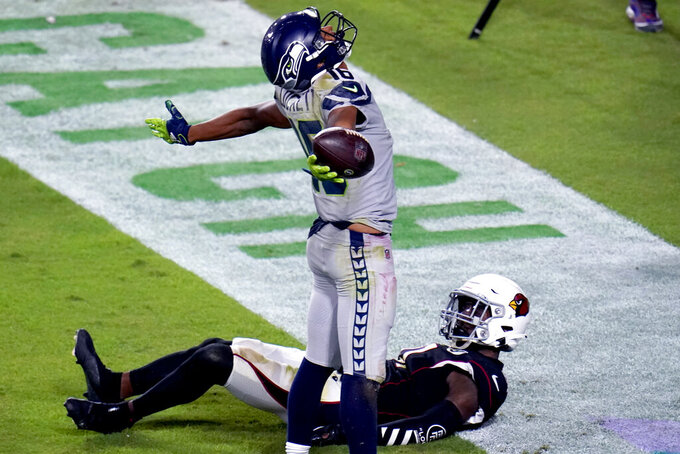 Seattle Seahawks wide receiver Tyler Lockett (16) celebrates his touchdown as Arizona Cardinals cornerback Patrick Peterson looks up during the first half of an NFL football game, Sunday, Oct. 25, 2020, in Glendale, Ariz. (AP Photo/Ross D. Franklin)