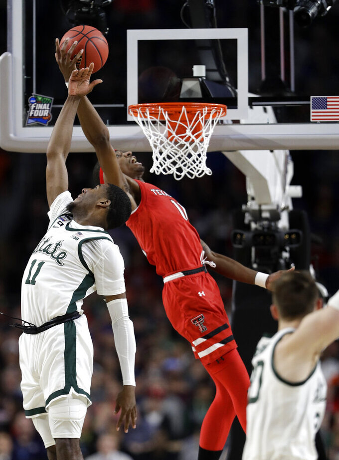 Michigan State forward Aaron Henry, left, fights for a rebound with Texas Tech forward Tariq Owens during the first half in the semifinals of the Final Four NCAA college basketball tournament, Saturday, April 6, 2019, in Minneapolis. (AP Photo/David J. Phillip)