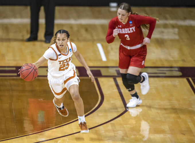 Texas guard Ashley Chevalier (25) brings the ball up as Bradley guard Gabi Haack trails during the first half of a college basketball game in the first round of the NCAA women's tournament at Strahan Arena in San Marcos, Texas, Monday, March 22, 2021. (AP Photo/Ricardo B. Brazziell)