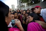 Relatives of prisoners watch in a mobile phone a video released by the prisoners outside of Venezuelan political police headquarters, SEBIN, in Caracas, Venezuela, Wednesday, May 16, 2018. In two short videos shot on a cell phone and posted Wednesday on his Facebook page U.S jailed citizen Joshua Holt said his life was threatened during a disturbance by inmates that include President Nicolas Maduro's top opponents. Venezuela's chief prosecutor sent a commission to the jail to discuss the prisoners' demands. (AP Photo/Fernando Llano)
