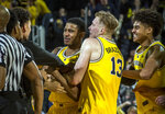 Michigan guard Charles Matthews, center, celebrates his game-winning buzzer-beater with forward Ignas Brazdeikis (13) and guard Jordan Poole, right, after an NCAA college basketball game against Minnesota at Crisler Center in Ann Arbor, Mich., Tuesday, Jan. 22, 2019. Michigan won 59-57. (AP Photo/Tony Ding)