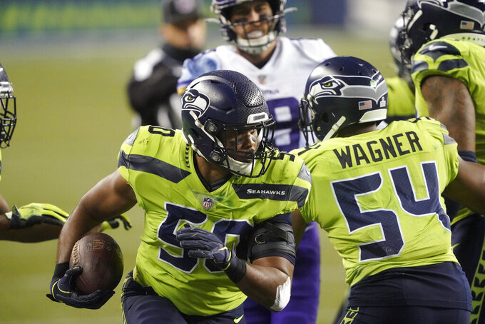 FILE - In this Sunday, Oct. 11, 2020, file photo, Seattle Seahawks' K.J. Wright runs with the ball after recovering a Minnesota Vikings fumble during the second half of an NFL football game, in Seattle. Once he became established in the NFL, Wright regularly said his goal was to make it 10 seasons in the league and then evaluate his next steps. The way Wright is playing this season for the Seahawks, his 10th in the league, there may be more seasons to come. (AP Photo/Ted S. Warren, File)