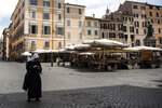 A nun checks her smartphone as she walks in Campo dei Fiori Square, in Rome, Wednesday, May 20, 2020. (AP Photo/Alessandra Tarantino)
