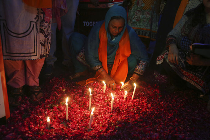A Pakistani woman lights candles during a vigil for the victims of bomb explosions in churches and hotels in Sri Lanka, in Lahore, Pakistan, Tuesday April 23, 2019. The death toll from the Easter Sunday bombings in Sri Lanka, rose Tuesday to more than 300.  (AP Photo/K.M. Chaudary)
