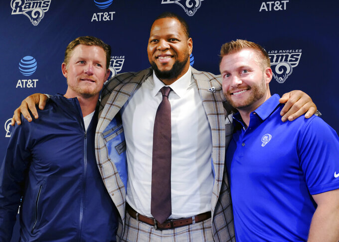 FILE - In this April 6, 2018, file photo, Los Angeles Rams new defensive tackle Ndamukong Suh, center, poses for a photo after a news conference with coach Sean McVay, right, and general manager Les Snead at the NFL football team's practice facility in Thousand Oaks, Calif. The excitement of the Rams' incredible one-season turnaround wasn't ruined by one defeat. Yet that loss was a signal to Snead, who decided it was time to do everything possible to help homegrown stars Todd Gurley, Aaron Donald and Jared Goff. So the Rams made several enormous bets on themselves, and every single one of them has paid off. (AP Photo/Richard Vogel, File)