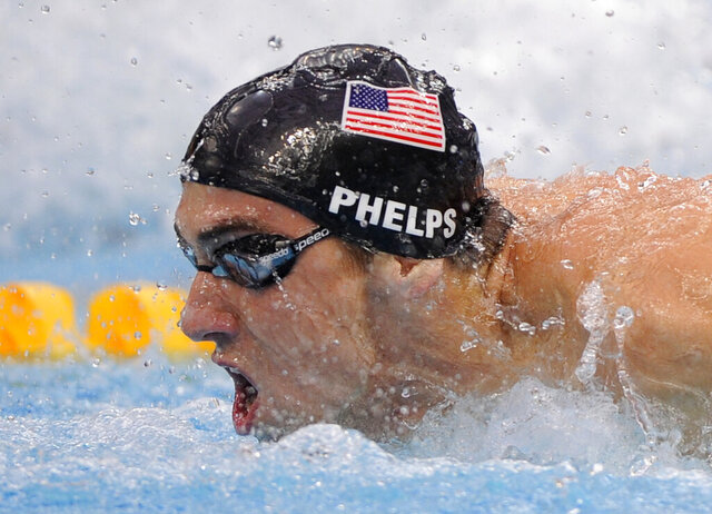 """File-United States Michael Phelps swims to the gold in the men's 4x100-meter medley relay final during the swimming competitions in the National Aquatics Center at the Beijing 2008 Olympics in Beijing, Sunday, Aug. 17, 2008.  The Olympics are remembered for the stars. That was true in Beijing in 2008, and the stars were Phelps and Usain Bolt. But Beijing is also storied for its signature venues like the """"Bird's Nest"""" stadium, and the """"Water Cube"""" swimming venue. No Olympics before — or since — have impacted a city the way the Olympics did Beijing. (AP Photo/Mark J. Terrill, File)"""