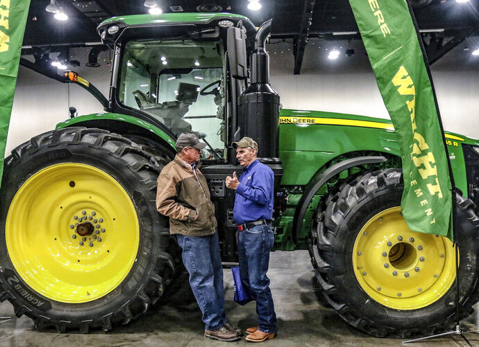 Larry Krampe of Rome, Ky, left, talks with Bill Brey of Whitesville, Ky while the two stand next to a John Deere model 8345 R tractor on display inside the Owensboro Convention Center during the 46th annual Ag Expo, Wednesday, Jan. 29, 2020, in Owensboro, Ky. (Greg Eans/The Messenger-Inquirer via AP)