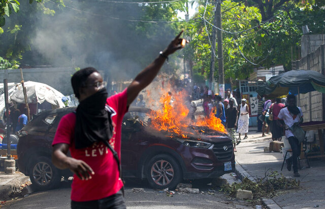 A protester holds up matches after setting a government car on fire during a protest demanding justice for a student who was gunned down by police the previous week at the university where students were protesting on campus for government teaching jobs in Port-au-Prince, Haiti, Monday, Oct. 5, 2020. (AP Photo/Dieu Nalio Chery)
