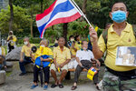 Elderly supporters of the Thai monarchy sit and watch as others wave Thai national flags and sing during a rally at Lumphini park in central Bangkok, Thailand Tuesday, Oct. 27, 2020.  Hundreds of royalists gathered to oppose pro-democracy protesters' demands that the prime minister resign, constitution be revised and the monarchy be reformed in accordance with democratic principles. (AP Photo/Gemunu Amarasinghe)