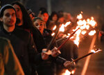 People walk holding torches as they take part in the