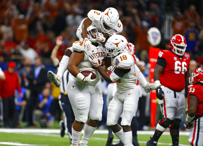 Texas defensive lineman Gerald Wilbon (94) celebrates his fumble recovery with defensive backs Kris Boyd (2) and Davante Davis (18) during the first half of the Sugar Bowl NCAA college football game against Georgia in New Orleans, Tuesday, Jan. 1, 2019. (AP Photo/Butch Dill)