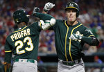 Oakland Athletics' Jurickson Profar (23) and Mark Canha, right, celebrate a solo home run by Canha in the fourth inning of the second baseball game of a doubleheader against the Texas Rangers in Arlington, Texas, Saturday, June 8, 2019. (AP Photo/Tony Gutierrez)