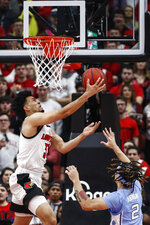 Louisville forward Jordan Nwora (33) shoots a reverse layup in front of North Carolina guard Cole Anthony (2) during an NCAA college basketball game Saturday, Feb. 22, 2020, in Louisville, Ky. (AP Photo/Wade Payne)