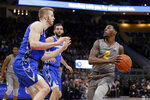 Marquette's Sacar Anim drives to the basket against multiple Creighton defenders during the first half of an NCAA college basketball game Tuesday, Feb. 18, 2020, in Milwaukee. (AP Photo/Aaron Gash)