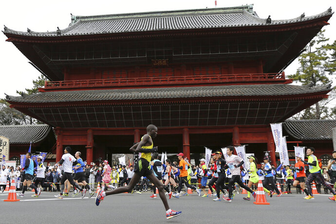 FILE - In this Feb. 23, 2014, file photo, runners pass by Zojoji Buddhist temple during the Tokyo Marathon in Tokyo. Tokyo Metropolitan Government was considering making a proposal, the start times at 3 a.m. or 5 a.m., hoping to keep the 2020 Tokyo Olympic marathon in Tokyo, Japanese news agency Kyodo News said on Thursday, Oct. 24, 2019. That could be proposed to Olympic organizers and the IOC, a move to keep the marathon from being moved out of Tokyo's summer heat to cooler summer weather 800 kilometers (500 miles) further north in Sapporo. (AP Photo/Eugene Hoshiko, File)