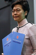 Hong Kong Chief Executive Carrie Lam holds copies of the policy statements for the media during a press conference at the Legislative Council in Hong Kong Wednesday, Oct. 16, 2019. In chaotic scenes, furious pro-democracy lawmakers twice forced Hong Kong's leader to stop delivering a speech laying out her policy objectives and clamored for her to resign after she walked out of the legislature on Wednesday and then delivered the annual address 75 minutes late via television. (AP Photo/Mark Schiefelbein)