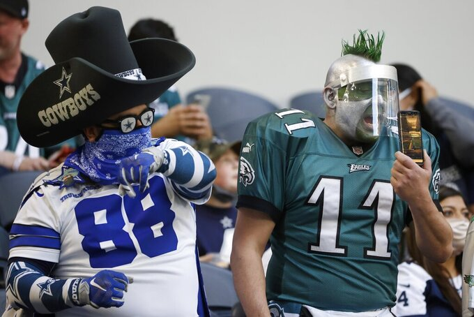 A Dallas Cowboys fan and Philadelphia Eagles fan cheer during the first half of an NFL football game in Arlington, Texas, Sunday, Dec. 27. 2020. (AP Photo/Ron Jenkins)