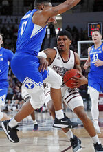 Mississippi State guard T.J. Gray (4) tries to dribble past Brigham Young guard Jahshire Hardnett (0) in the first half of an NCAA college basketball game in Starkville, Miss., Saturday, Dec. 29, 2018. (AP Photo/Rogelio V. Solis)