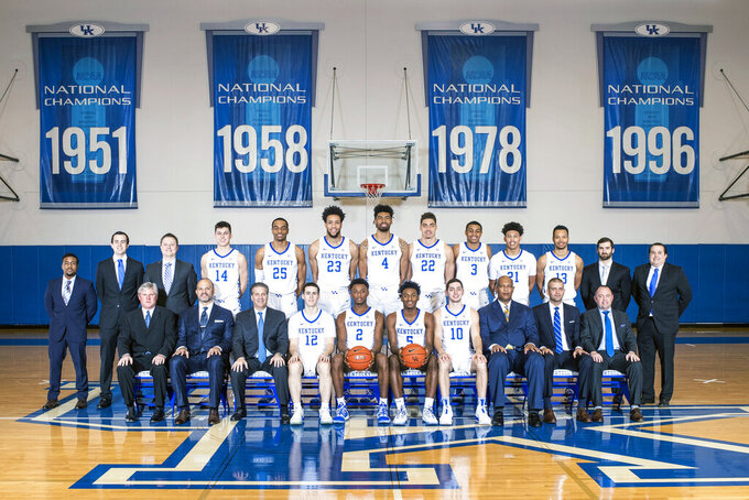 This photo provided by Kentucky Athletics shows the 2018-19 NCAA men's college basketball team. Seated from left are: Special assistant to the head coach John Robic, assistant coach Tony Barbee, head coach John Calipari, Brad Calipari, Ashton Hagans, Immanuel Quickley, Jonny David, associate head coach Kenny Payne, assistant coach Joel Justus and assistant athletic director for basketball operations Chris Woolard. Standing from left are: Strength coach Robert Harris, recruiting analyst Brady Kennedy, director of basketball administration Will Barton, Tyler Herro, PJ Washington, EJ Montgomery, Nick Richards, Reid Travis, Keldon Johnson, Zan Payne, Jemarl Baker Jr., assistant strength coach Cameron Bird, and equipment manager Mark Evans. (Chet White/Kentucky Athletics via AP)