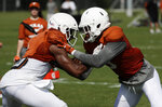 Texas wide receiver John Burt, left, and wide receiver Collin Johnson, right, go through drills during a morning practice at the NCAA college football team's facility in Austin, Texas, Wednesday, Aug. 7, 2019. (AP Photo/Eric Gay)