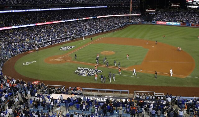 FILE - In this Nov. 1, 2017, file photo, the Houston Astros celebrate after Game 7 of baseball's World Series against the Los Angeles Dodgers in Los Angeles. The Astros won 5-1 to win the series 4-3. The Astros are returning to Dodger Stadium. The Dodgers won't be there, but their fans surely won't let the visitors forget. While the Dodgers head to Texas for the NL Division Series, their ballpark is hosting the American League Division Series in a postseason relocated due to the coronavirus pandemic. On Monday, Oct. 5, the Astros and the Oakland Athletics will open their ALDS matchup at Dodger Stadium. (AP Photo/Matt Slocum, File)