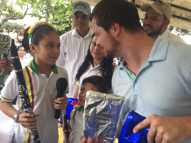 This 2017 photo provided by Nancy Hoddinott, Luke Putney, right, delivers donated instruments during a trip for the non-profit he started, Instrumental Horizons, in Colombia   Putney came home from a mission trip with what he thought was a bad headache.Instead, doctors found a brain tumor.  While the initial surgery to remove the tumor went well, he eventually suffered a stroke that ended him in the hospital for 100 days and left him without the ability to walk or care for himself.When he left the hospital, Putney said he wanted every step of his recovery to be dedicated to making the world a better place. (Nancy Hoddinott via AP) .