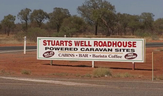 In this image made from video, an advertisement for the campsite line the roadside where a woman was found after being stranded in the Alice Springs area in the central Australian Outback. Tamra McBeath-Riley, 52, was being treated in an Alice Springs hospital for dehydration and exposure after she was found late Sunday, Police Superintendent Pauline Vicary said. The air search continued on Monday for her friends Claire Hockridge, 46, and Phu Tran, 40. (Australian Broadcasting Corporation via AP)