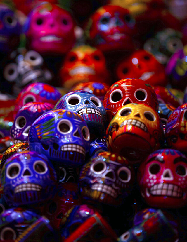 Miniature Day of the Dead ceramic skulls are displayed for sale at the Jamaica Market, in Mexico City, Thursday, Oct. 29, 2020. Mexico's Day of the Dead celebration this weekend won't be the same in a year so marked by death, in a country where more than 90,000 people have died of COVID-19. Many of those had to be cremated rather than buried, and even for those with gravesides to visit, the pandemic has forced authorities in most parts of Mexico to close cemeteries to prevent the traditional Nov. 1-2 observances when entire families clean and decorate tombs. (AP Photo/Fernando Llano)