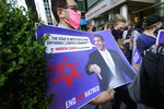 A manholds a sign as he joins protesters outside the offices of New York Gov. Andrew Cuomo, Thursday, Oct. 15, 2020, in New York. Three Rockland County Jewish congregations are suing New York state and Gov. Andrew Cuomo, saying Cuomo engaged in a