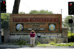 FILE - In this Aug. 9, 2009, file photo, a woman takes a photograph at the entrance of the California Institution For Men State Prison Chino, Calif. California lawmakers harshly criticized state corrections officials Wednesday, July 1, 2020, for a