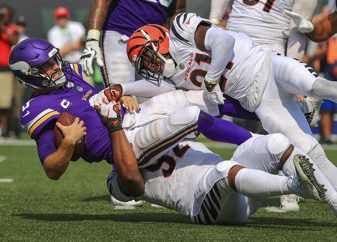 Cincinnati Bengals defensive end Noah Spence (52) and cornerback Mike Hilton (21) sack Minnesota Vikings quarterback Kirk Cousins (8) during the second half of an NFL football game, Sunday, Sept. 12, 2021, in Cincinnati. (AP Photo/Aaron Doster)