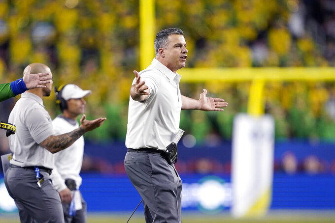 FILE - In this Dec. 6, 2019, file photo, Oregon head coach Mario Cristobal, right, gestures during the second half of the Pac-12 Conference championship NCAA college football game against Utah in Santa Clara, Calif. (AP Photo/Chris Pietsch, File)