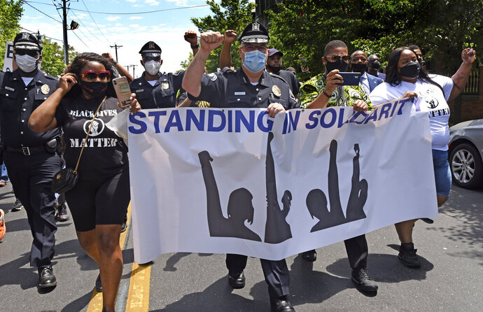In this Saturday, May 30, 2020, photo, Camden County Metro Police Chief Joe Wysocki raises a fist while marching with Camden residents and activists in Camden, N.J., to protest the death of George Floyd in Minneapolis. Police officers in one of New Jersey's largest and most violent cities were praised on social media for marching alongside protesters in rallies held this weekend over Floyd's death. (April Saul via AP)