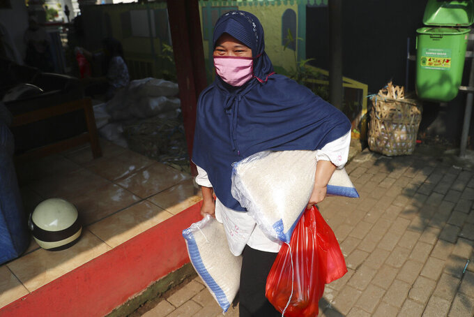 A woman wears a face mask as a precaution against the new coronavirus outbreak as she receives free staple food packages provided by the government for low-income residents in Jakarta, Indonesia, Thursday, June 11, 2020. (AP Photo/Achmad Ibrahim)