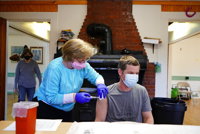 FILE- Maureen Giffen administers a COVID-19 vaccination to Josh Gray in a community center on Great Cranberry Island, Maine, Friday, March 19, 2021.  Maine's number of daily positive coronavirus cases continued to trend upward, Friday, April 23. The seven-day rolling average of daily new cases in Maine has risen over the past two weeks.  (AP Photo/Robert F. Bukaty, file)