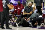 An official receives medical attention after being knocked down in the first half of an NCAA college basketball game between Oklahoma and TCU in Fort Worth, Texas, Sunday, Dec. 6, 2020. The official continued to work the game with a bump and a small cut to the forehead. (AP Photo/Tony Gutierrez)